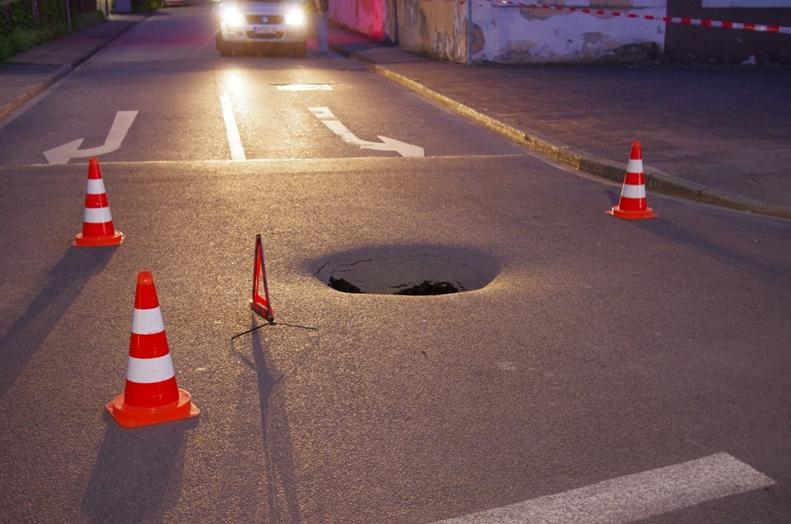 Kanaleinbrauch - ein kleines Loch tut sich in der Straßendecke auf.